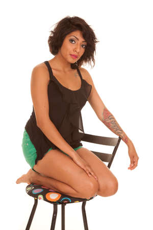 a Hispanic woman kneeling in a chair with a serious expression photo