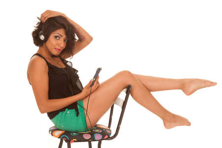 a Hispanic woman sitting on a chair and listening to music. photo