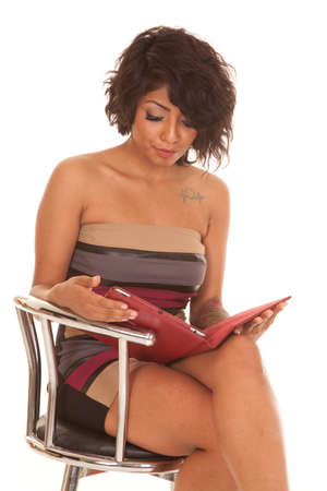 a Hispanic woman sitting and looking at her tablet with a serous expression. photo