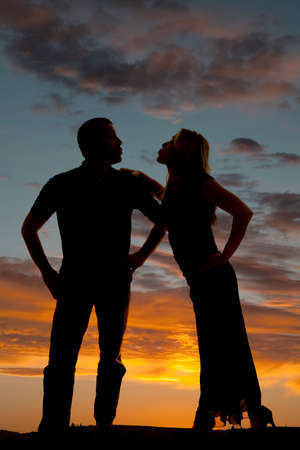 puckered lips: A silhouette of a man and a woman with their lips puckered up, with a beautiful sky behind them.