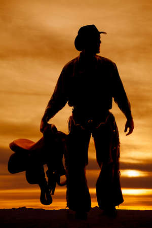 a silhouette of a cowboy holding on to his saddle. photo
