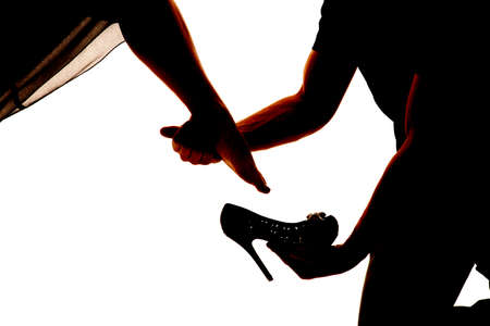 A silhouette of a man placing on a womans shoe. Stock Photo