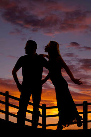 lean over: a silhouette of a woman trying to lean over and give her cowboy a kiss.