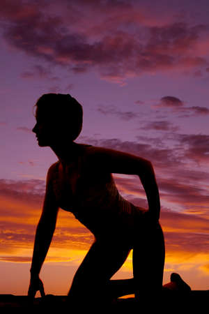 woman kneeling: A silhouette of a woman kneeling in the outdoors. Stock Photo