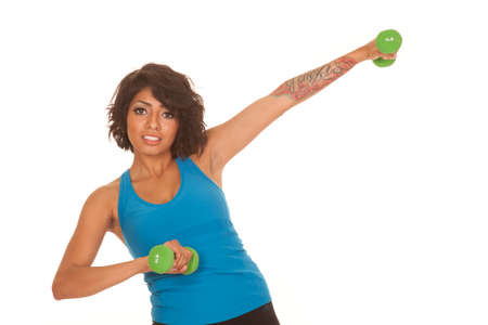 A Hispanic woman working out with weights and a tattoo on her arm. photo