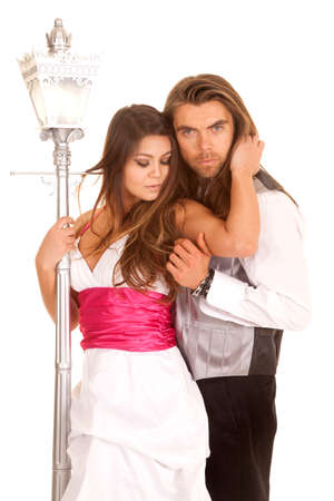 formals: A couple is dressed in formals is standing by a lamp post.