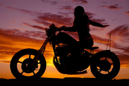 A woman on a motorcycle in the sunset with her arm back. photo