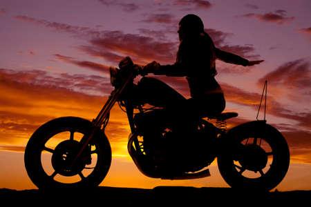 motorrad frau: Eine Frau auf einem Motorrad in den Sonnenuntergang mit dem Arm zur�ck.