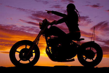 A woman on a motorcycle riding in the sunset pointing in front of her. photo