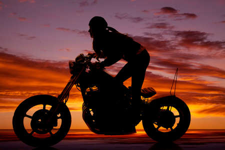 A woman riding a motorcycle in the sunset leaning forward photo