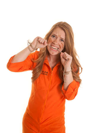 A woman in an orange jumpsuit in handcuffs biting a chain. Stock Photo - 24478712