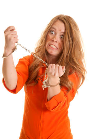 A woman in an orange jumpsuit in handcuffs looks crazy. photo