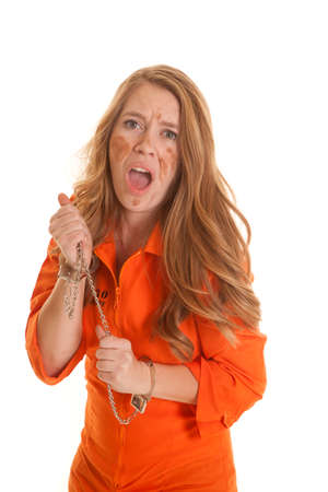 A woman in an orange jumpsuit in handcuffs mad. Banco de Imagens - 24478714