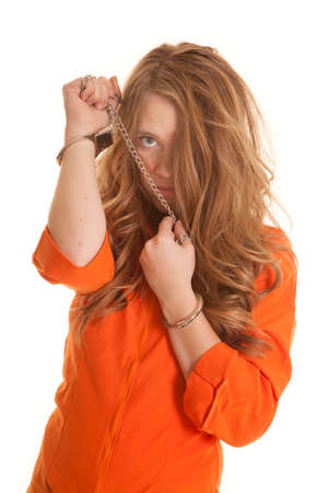 A woman in an orange jumpsuit in handcuffs with a chain. photo