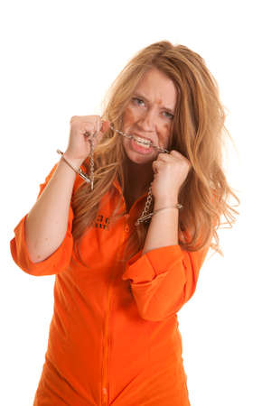 A woman in an orange jumpsuit in handcuffs biting a chain.