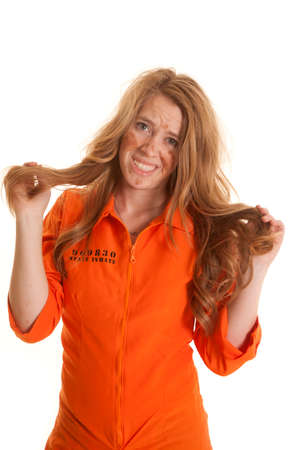 A woman in an orange jumpsuit has messed up hair.