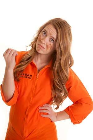 A woman in an orange jumpsuit looking at her finger nails.