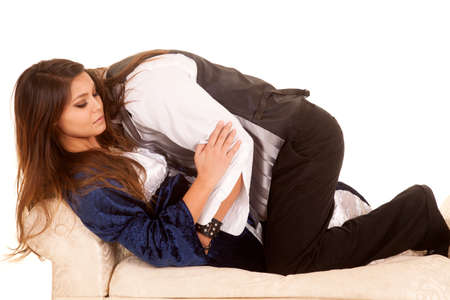 A man and woman dressed in the time period from the Renaissance, holding each other on the couch. Stock fotó