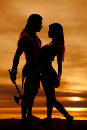 hatchet man: A man holding onto his weapon of war in one hand and his Indian woman in the other. Stock Photo