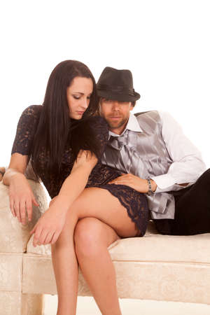 a couple sitting on a couch, he has his hand on her leg. photo