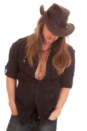 shirt unbuttoned: A cowboy with his shirt unbuttoned looking down. Stock Photo