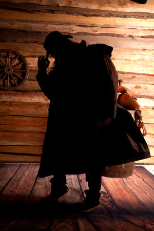 A silhouette of a cowboy in his duster looking down. photo