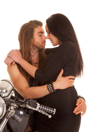 A man holding on to his woman on his motorcycle getting ready to kiss her. photo