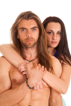A man without a shirt and his woman hanging on him from behind. photo