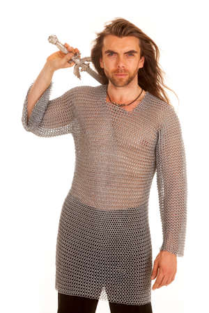 A man in chain mail holding on to his sword behind his back. photo