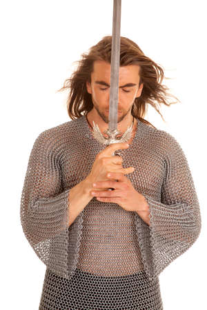 A man in his medieval chain mail leaning his head against his sword. photo