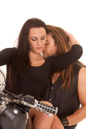 a woman with a man laying on her shoulder while they are sitting on a motorbike