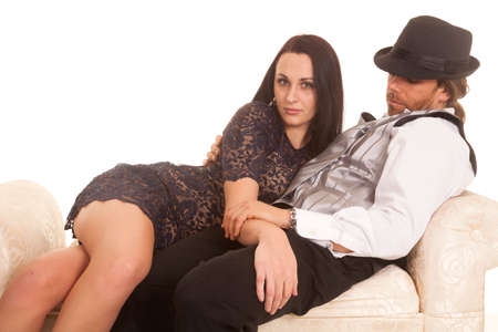 A woman laying on her man on the couch in formal wear.