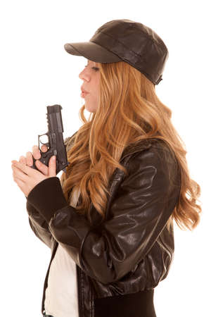 A woman in her leather jacket and hat blowing on the tip of her gun. photo