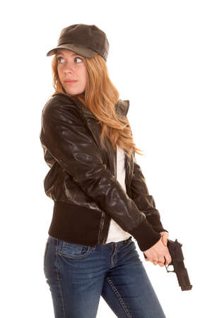 a woman in her leather jacket and hat pointing her gun down. photo