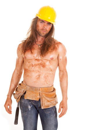 A man in his tool belt and hard hat with dirt and mud all over his body. photo