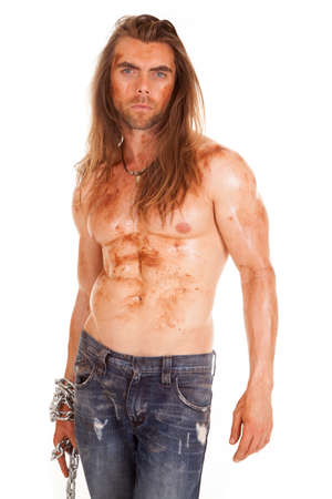 A man without a shirt holding on to a chain with mud on his body. photo