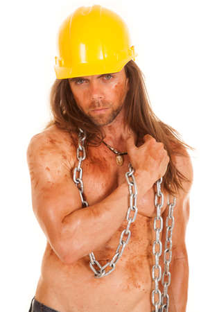a man in his hard hat with mud all over his body and face.  He is wearing his hard hat and hanging on to a chain. photo