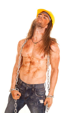 A man with mud and dirt all over his body wearing his hard hat with a chain wrapped around his body. photo