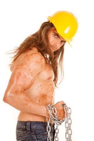A man in his construction hat with mud and dirt all over his face and body. photo