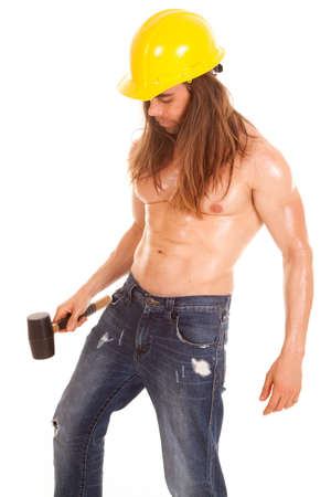 A man in his construction hat witha hammer in his hand looking down. photo