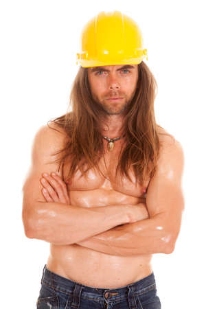 a man in his construction hat with his arms folded over his chest. photo