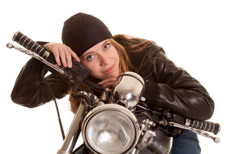 a woman in her leather jacket with a smile on her motorcycle photo