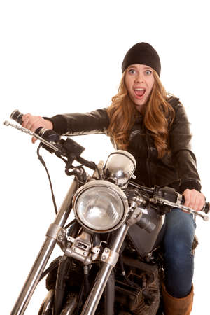 A woman sitting on her motorcycle with a shocked expression on her face. photo