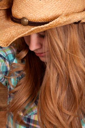 cowgirl hat: Una mujer con su sombrero de vaquera con la cabeza mirando hacia abajo.