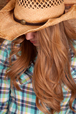 a cowgirl looking down so you can not see her face Imagens