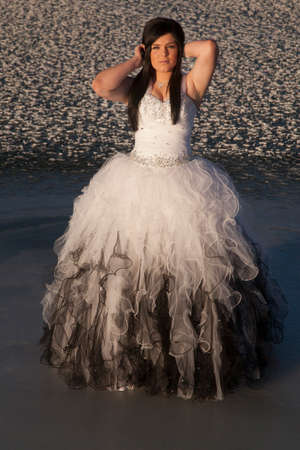 A woman in her formal gown standing in the outdoors on a frozen lake. Stock Photo - 24936509