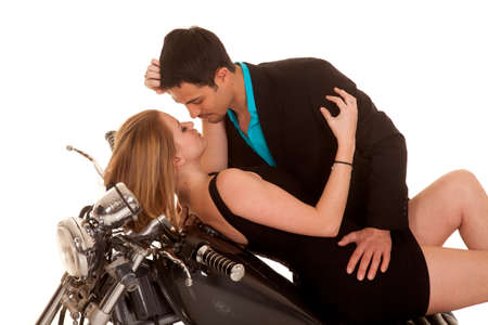 A couple laying back on her motorcycle getting ready to kiss. photo