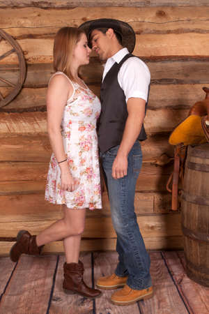 A cowboy is about to kiss his cowgirl in front of a wooden wall.