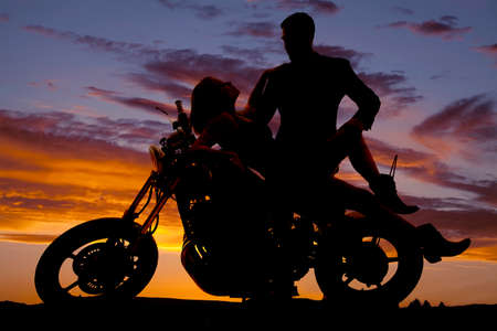 romance: Una silueta de una mujer puesta en la moto con su hombre mirándola. Foto de archivo