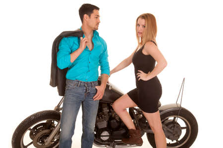 handle bars: Una mujer de pie junto a una moto y su hombre apoyado en el manillar.